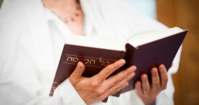 person dressed in white holding prayer book