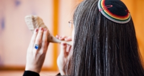 woman wearing rainbow kippah blowing shofar