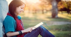 young woman reading outside