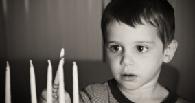 black and white photo of little boy lighting hanukkah candles