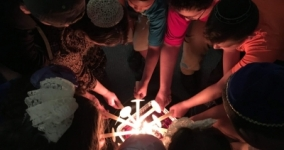 people in circle bringing individual candles together to light as one