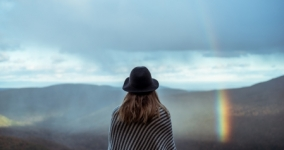 woman in hat looking out toward mountains and rainbow
