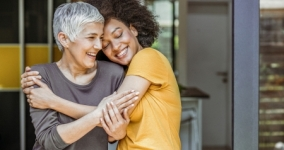 older white woman hugging younger black woman