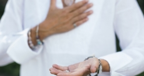person in white blouse with one hand on heart and one hand open in front