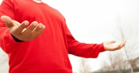 black man in red shirt with hands open in prayer