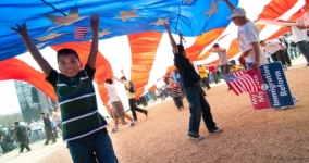 people holding up giant american flag, hispanic boy in foreground smiling