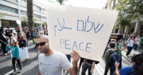 man in protest holding sign that says peace in english and hebrew