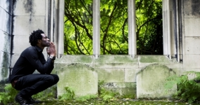man squatting in contemplation in graveyard