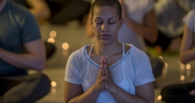 brown woman with close cropped hair sitting in meditation with other meditators and candles in background