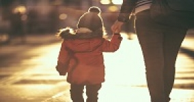 back view of a woman walking down the street holding the hand of a young child