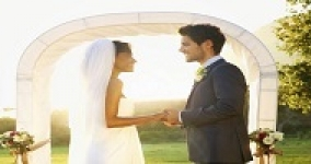man and woman holding hands before a wedding chuppah