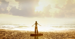 Woman standing at shore with arms open and sun shining