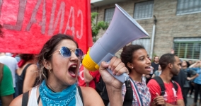 young woman shouting into megaphone at protest