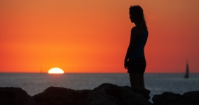 silhouette of woman standing at sea at sunset