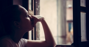 woman looking out window with sad expression