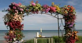 chuppah decorated with flowers with water in the background