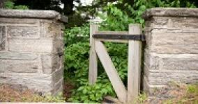 wooden gate between two stone pillars