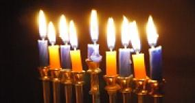 close picture of yellow and blue candles burning in a hannukkiah