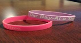 two bracelets, one purple one pink with the words one day at a time