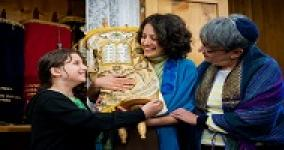 three generations of women passing a torah