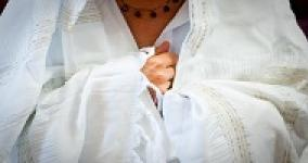 person wearing a white prayer shawl (tallit) holding hands together