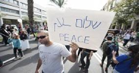 protest walk with man holding a sign that says shalom in hebrew, salaam in arabic and peace in english