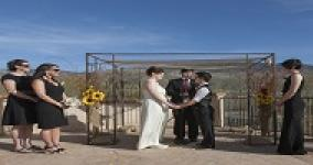 two women holding hands getting married underneath a chuppah