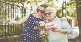 young woman taking photo of her and elderly woman holding a present