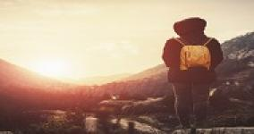 person standing with backpack facing a sunset