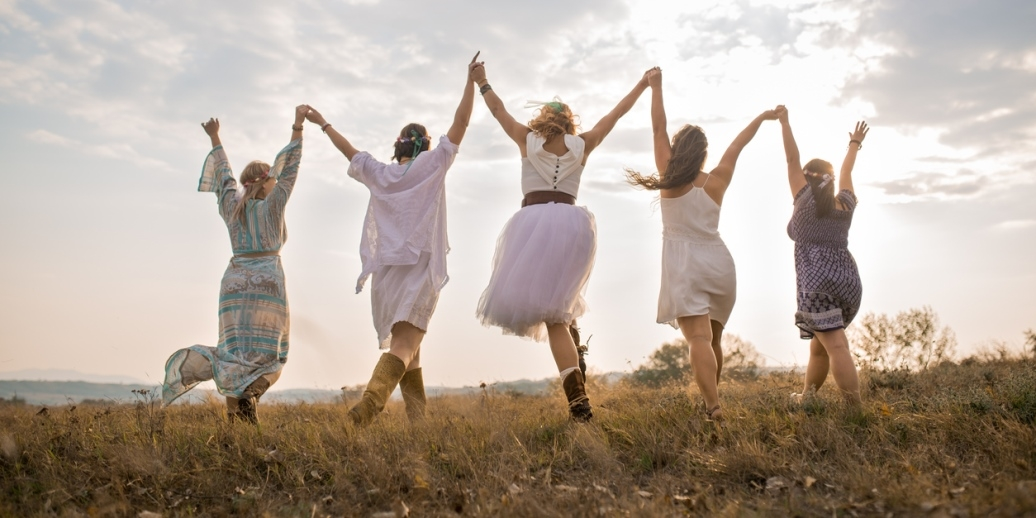 Friends holding hands jumping