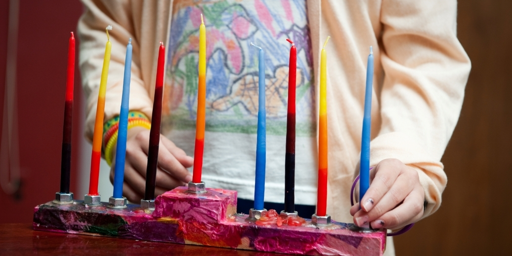 girl lighting hanukkah candles