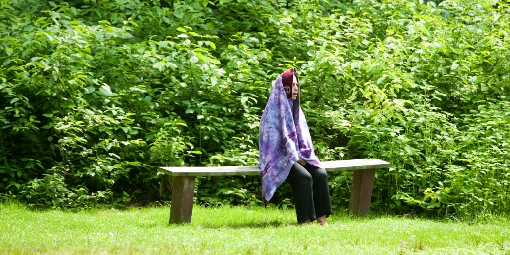 person wrapped in purple tallit sitting on bench meditating surrounded by trees