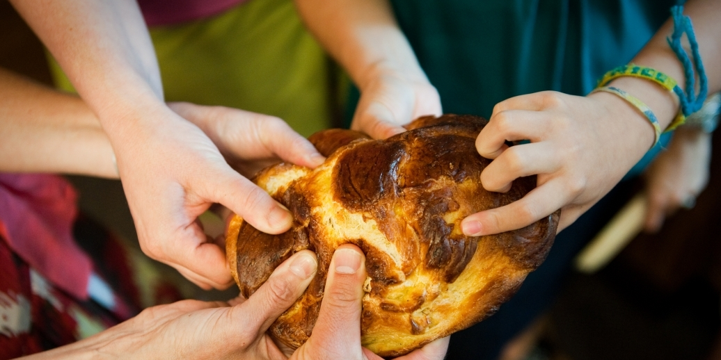 hands touching challah