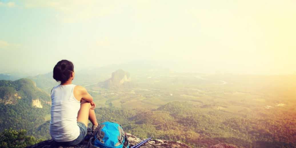 Woman sitting on mountain look at sunny view