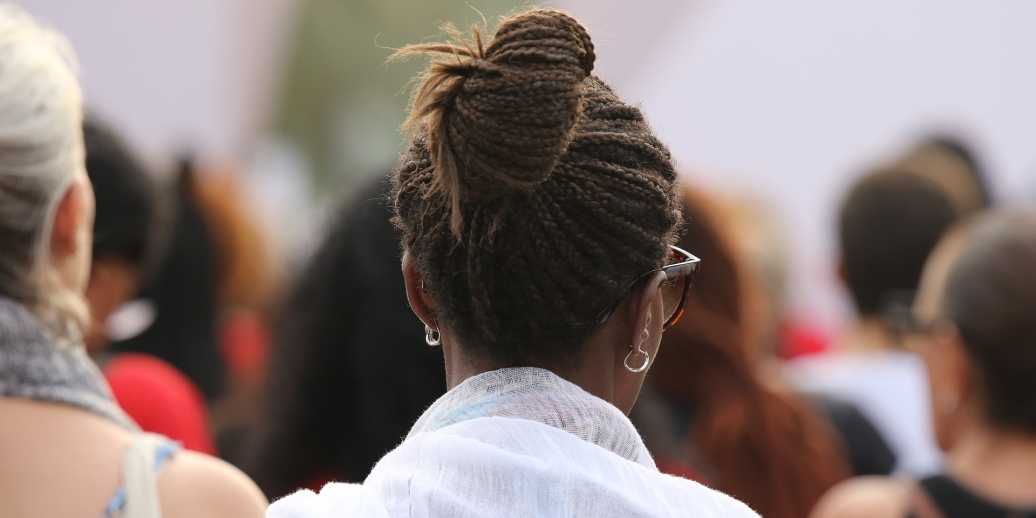black woman wearing white shawl in a crowd shown from behind