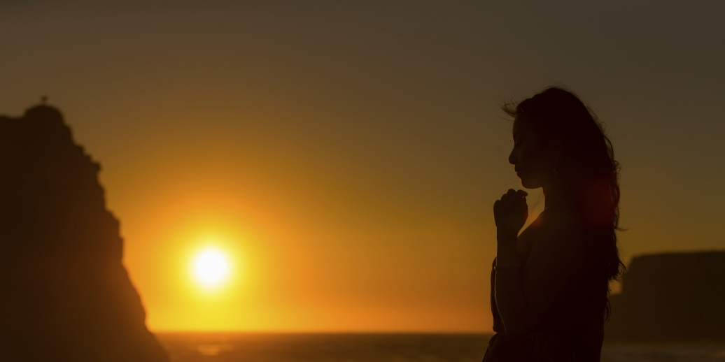 woman in silhouette, head bowed in prayer, by the ocean at sunset