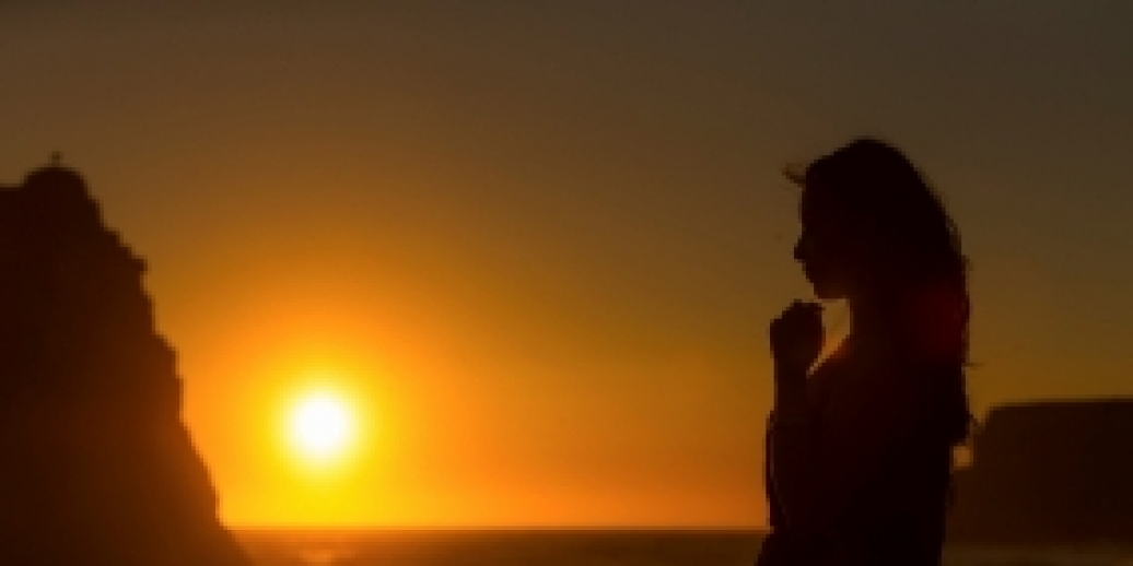 silhouette of woman praying with sun setting behind her