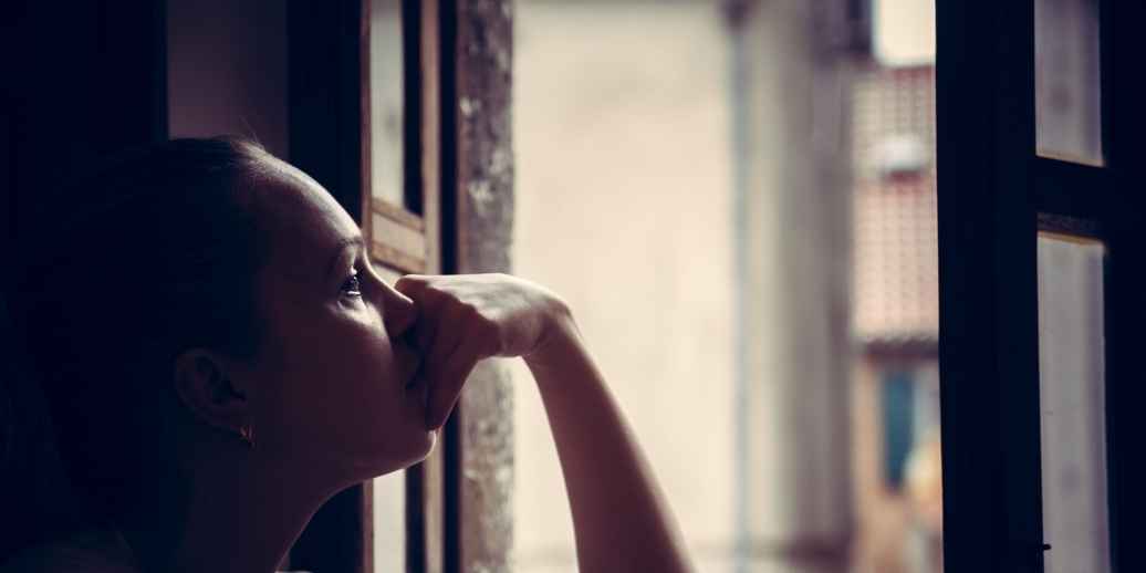 woman looking out window with sad expressions
