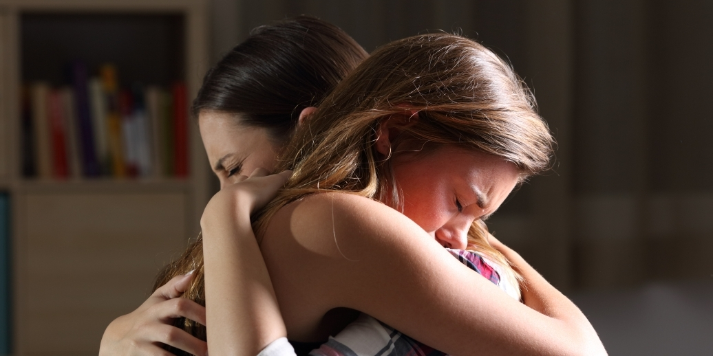two women embracing in grief