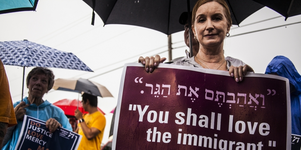 """woman holding sign """"you shall love the immigrant"""""""