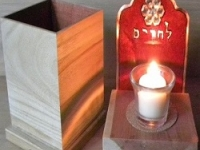 yizkor box and candle with red background, trellis background