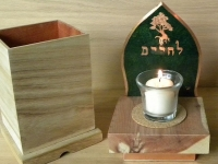 yizkor box and candle with green background in the shape of a flame