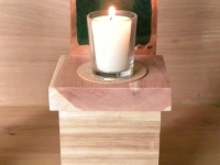 votive candle on a wood box with a emerald background with word yizkor