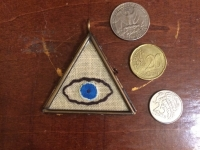 triangle pendant with stitched eye in the center, size of 2 quarters